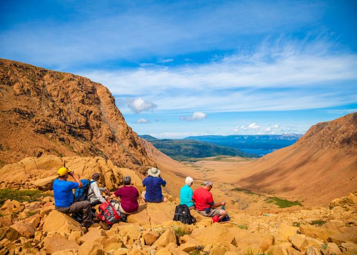 A group of six older hikers take a moment to rest and take in the scenery on the tablelands at Gros Morne National Park.