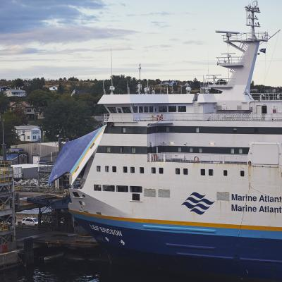 Vehicles prepare to board the open bridge of the Leif Ericson ferry, which is blue and white with a teal and yellow stripe.
