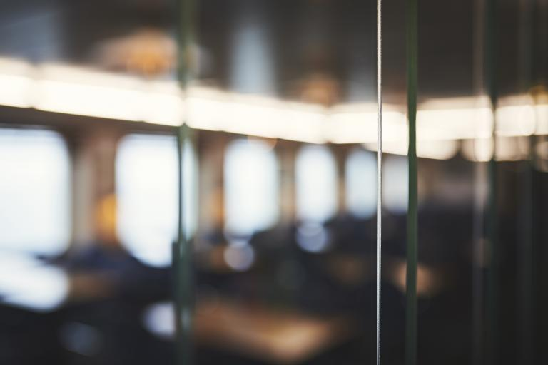 A blurry, unfocused image of a window overlooking what might be a seating area inside a Marine Atlantic ferry.