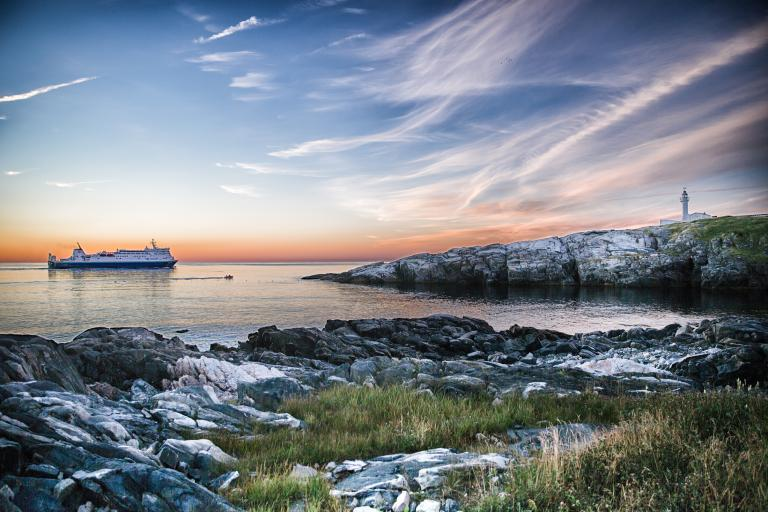 A Marine Atlantic ferry sails along the Avalon Peninsula at sunset towards the Cape Spear Lighthouse in Newfoundland.