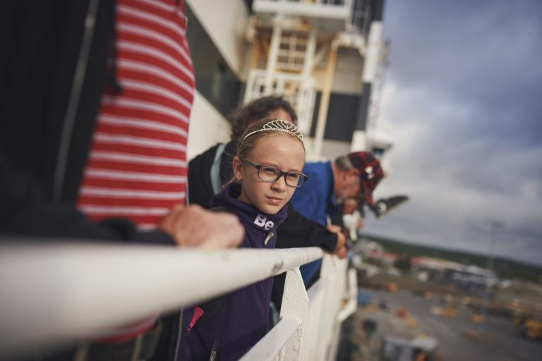 A young girl wearing a tiara and her family look over the white rails of a Marine Atlantic ferry as it leaves port.