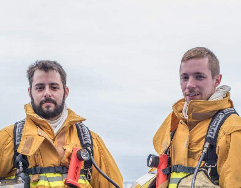 Two firefighters standing outside